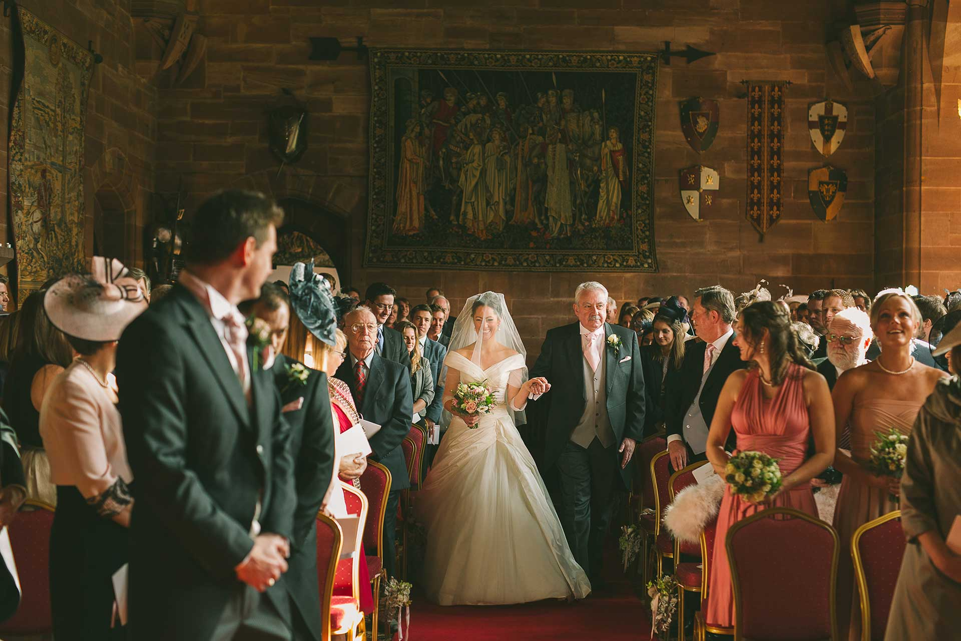 A peckforton castle bride makes her way down the aisle, taken by Qualified Shropshire Wedding Photographer Phil Barrett BA(hons) LMPA