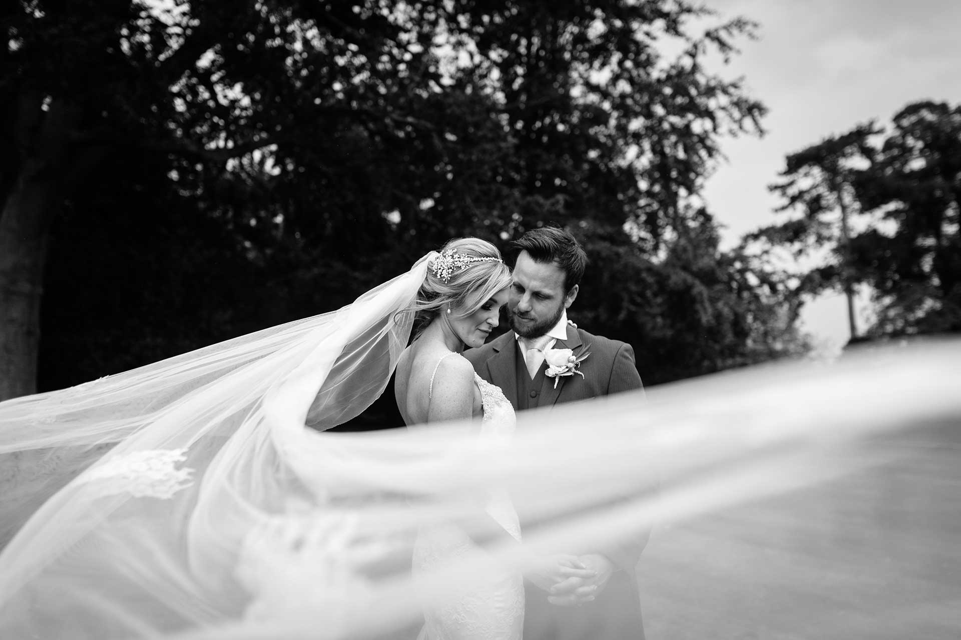 A cheshire bride and groom being caught by Qualified Shropshire Wedding Photographer pbartworks as the brides veil wraps around her