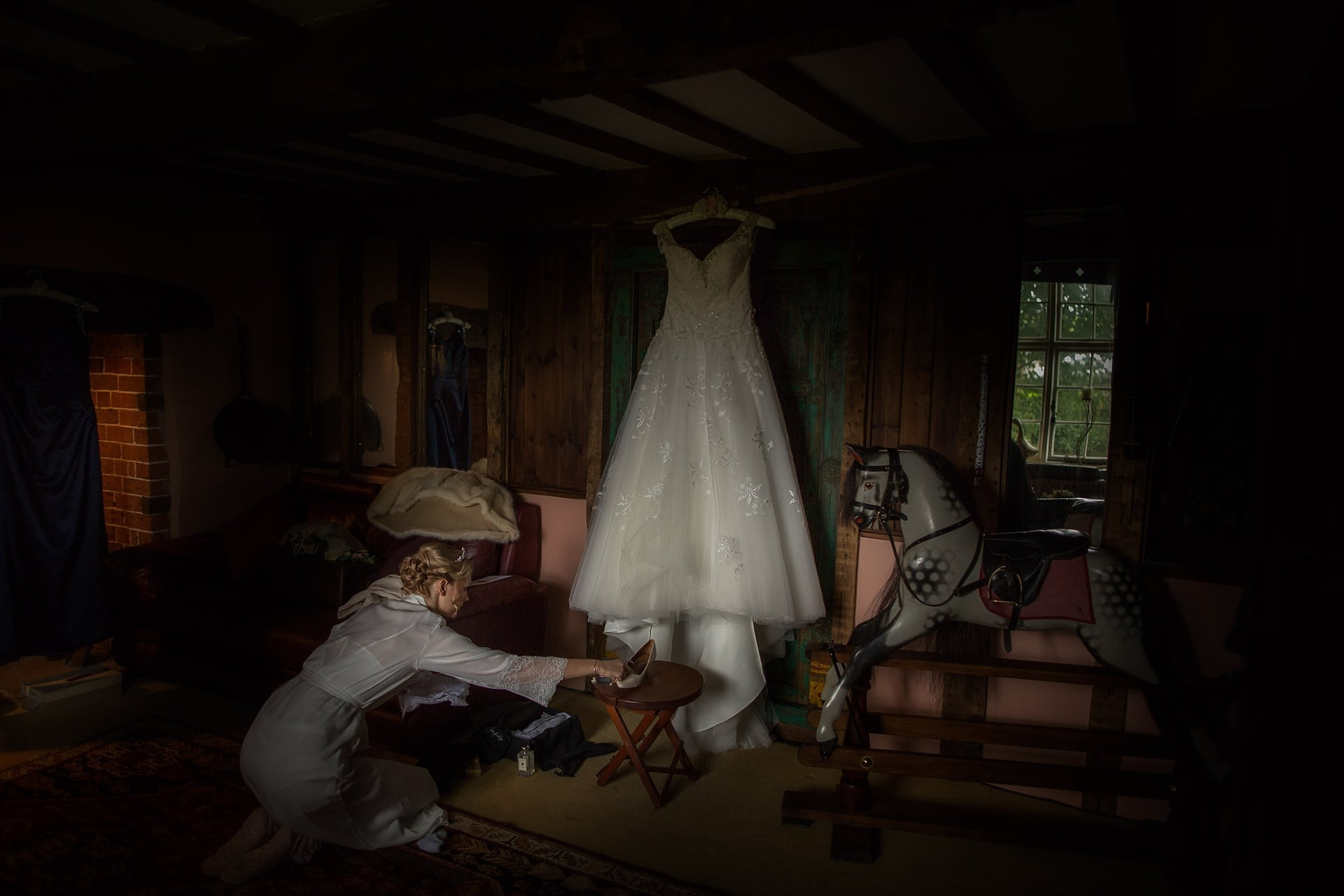 Sarah places her shoes by her dress, while Shropshire Documentary wedding photographer pbartworks captures the scene