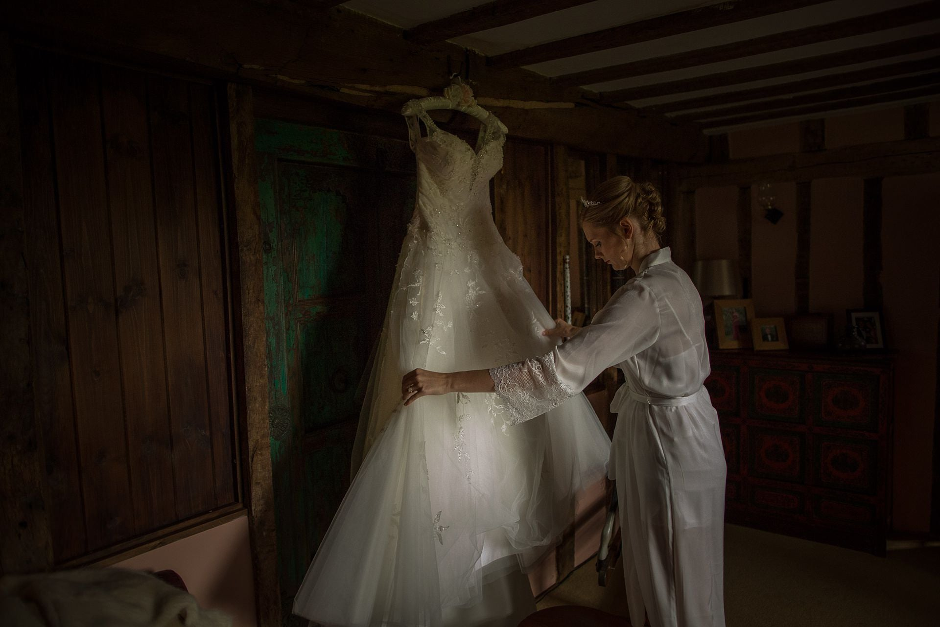 Shropshire Documentary Wedding Photographer pbartworks captures Sarah tending to her dress before leaving for Delbury Hall