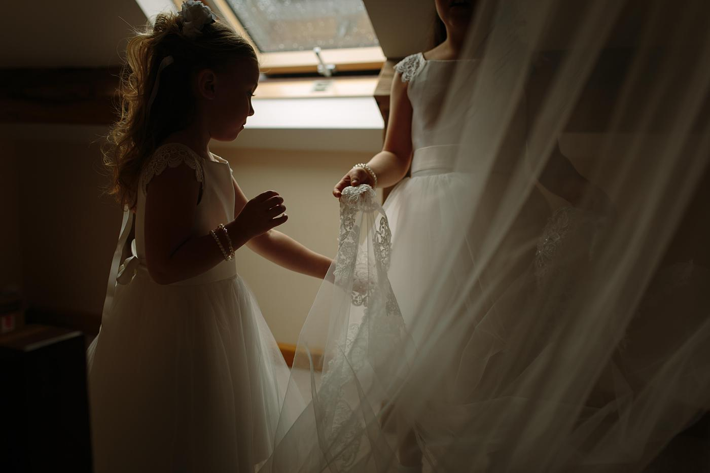 flower girls playing with a brides veil