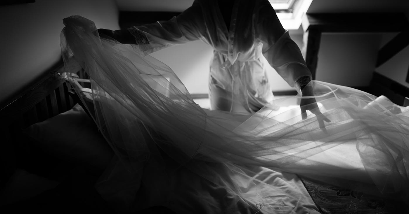 a candid moment as a bride lays out her veil and wedding dress