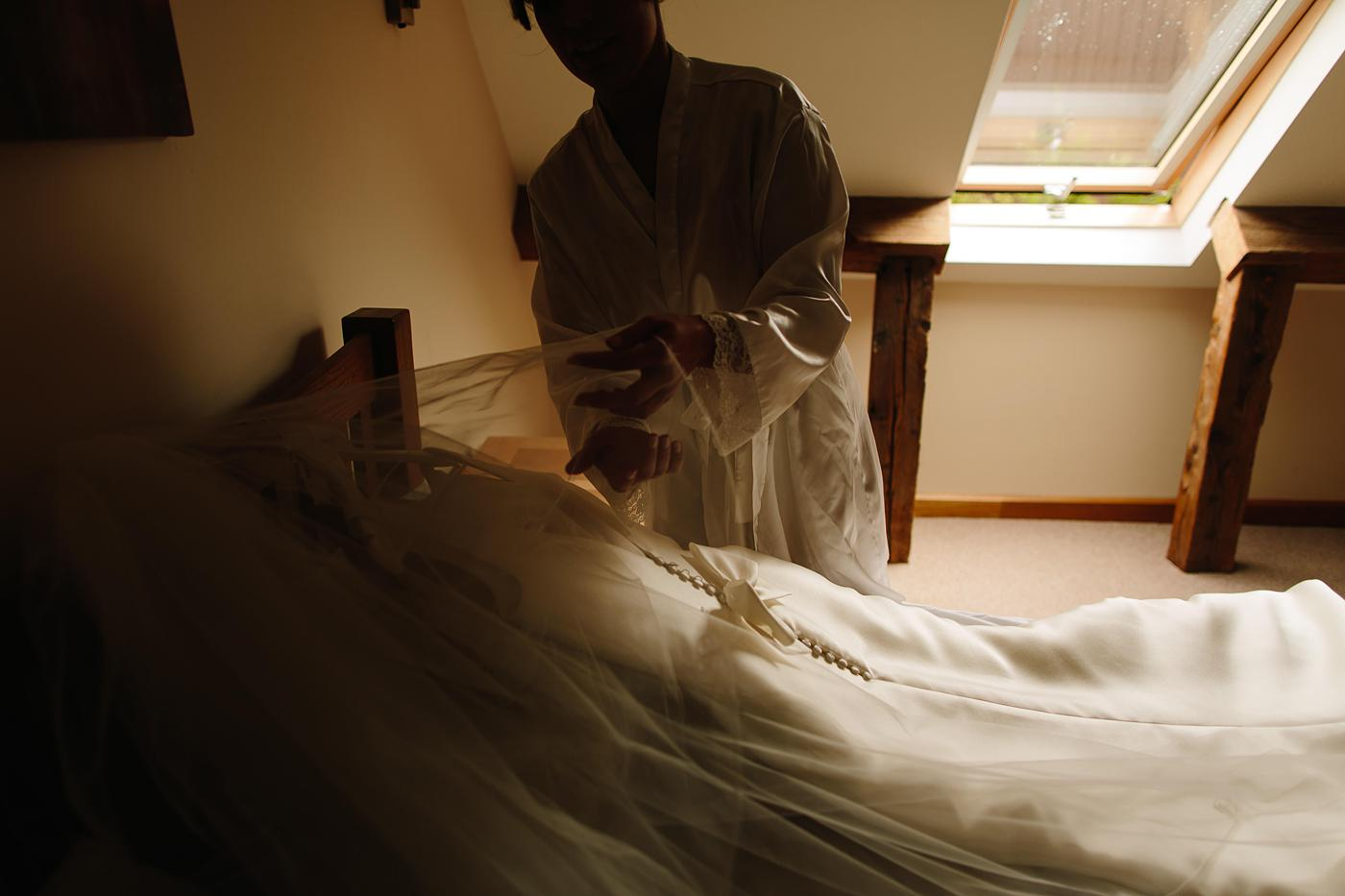 a wedding dress being arranged by the bride