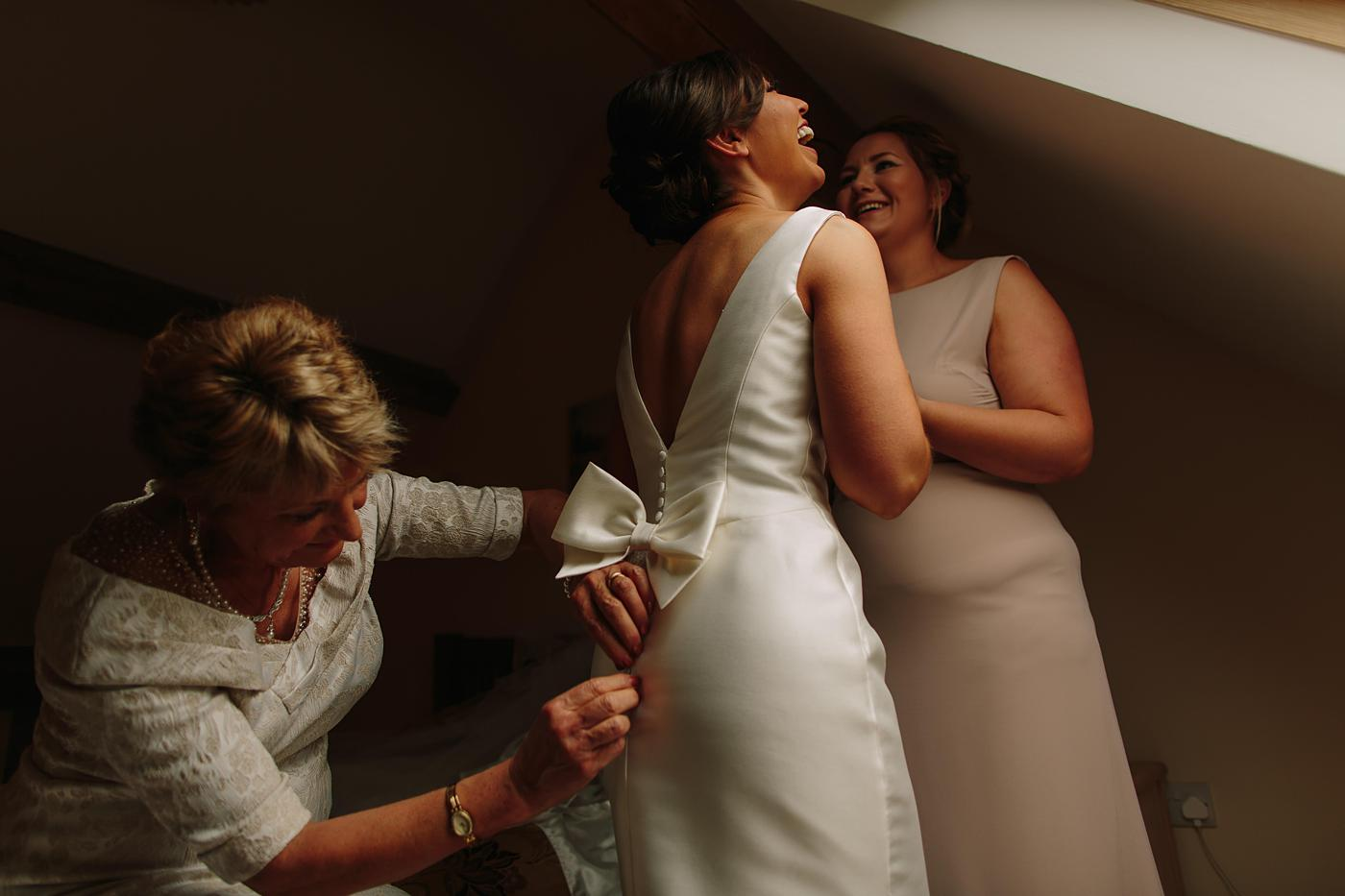bride with her Mother and bridesmaid being fastened into her dress