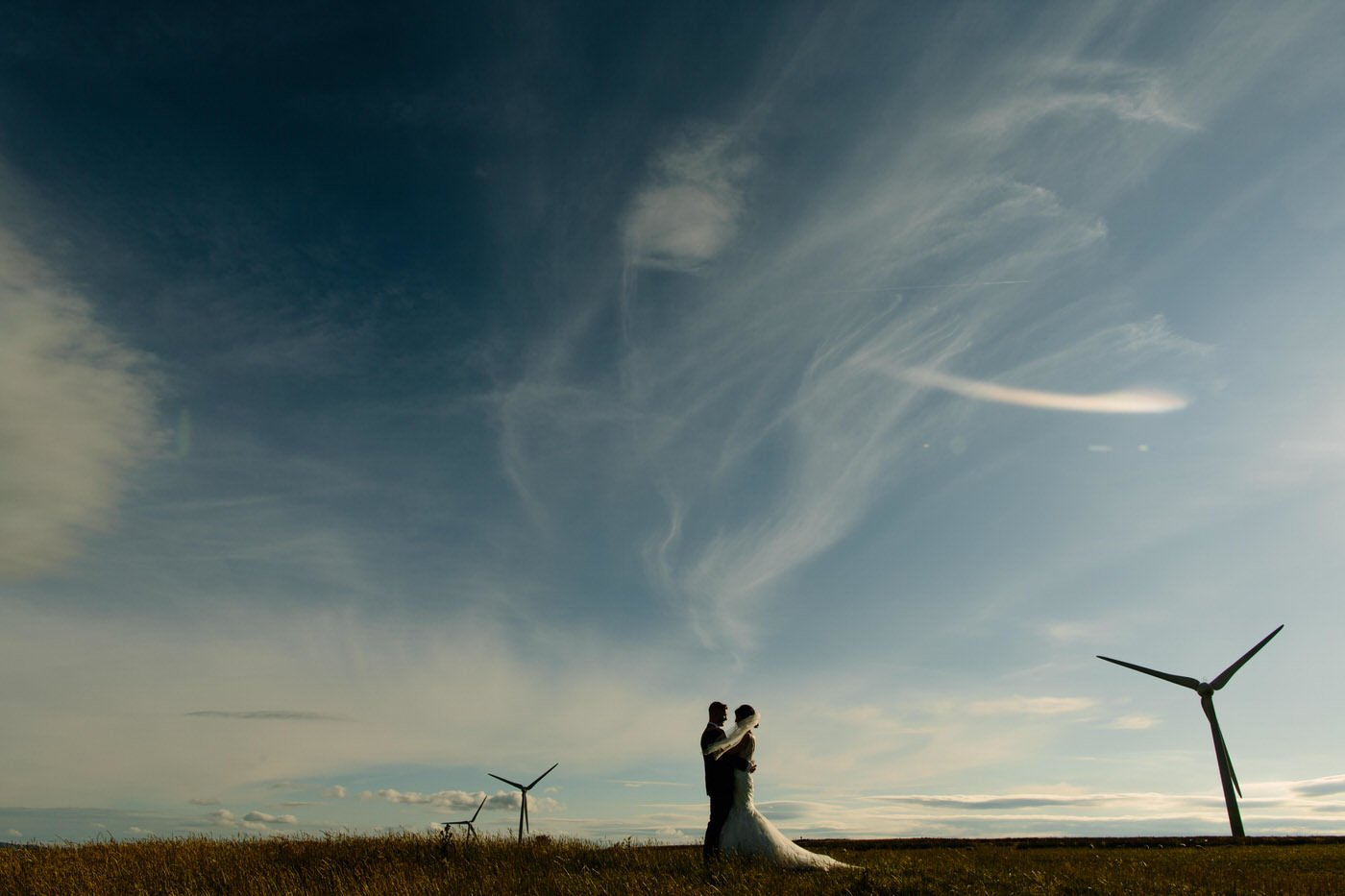Bride and Groom set against wind turbines at a North Wales Wedding