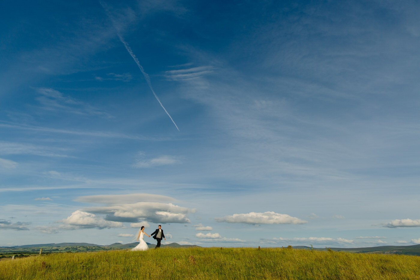 Bride and Groom walk across welsh hillside at a North Wales Wedding