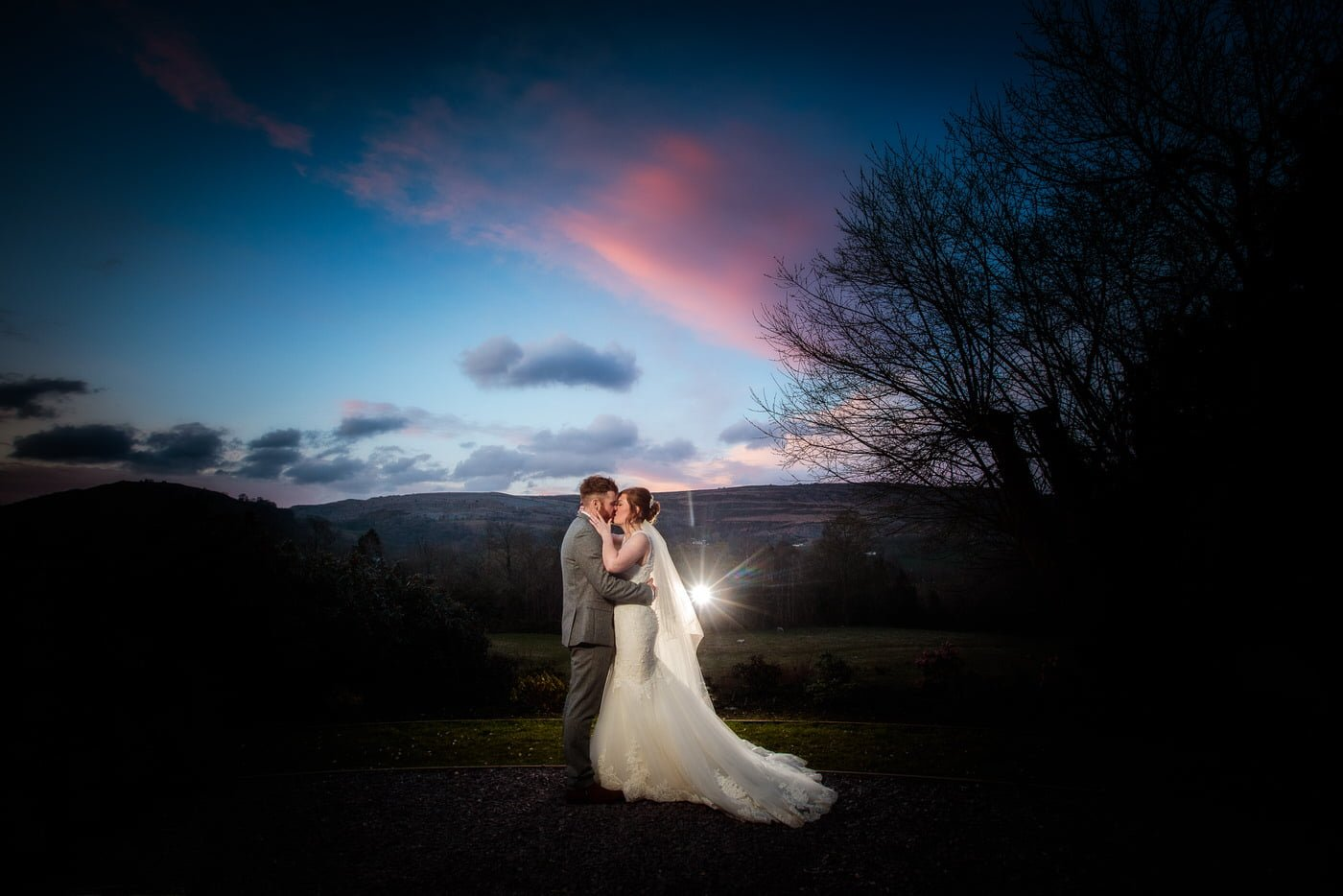 at a Tyn Dwr Hall Wedding the bride and groom take time out to enjoy the sunset and share a kiss