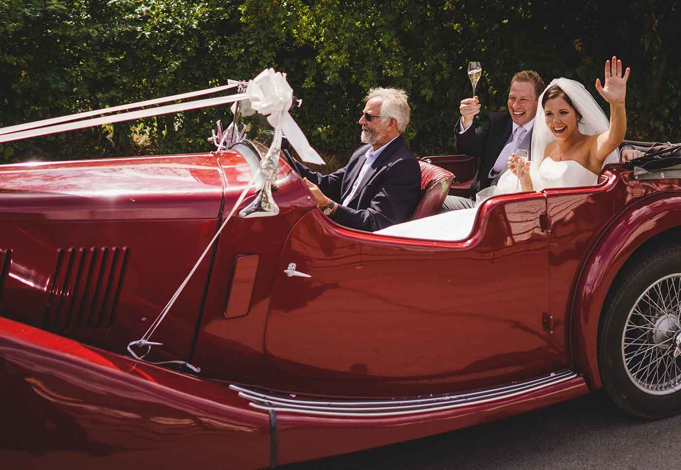 Car leaving a Church in North Wales with bride and groom