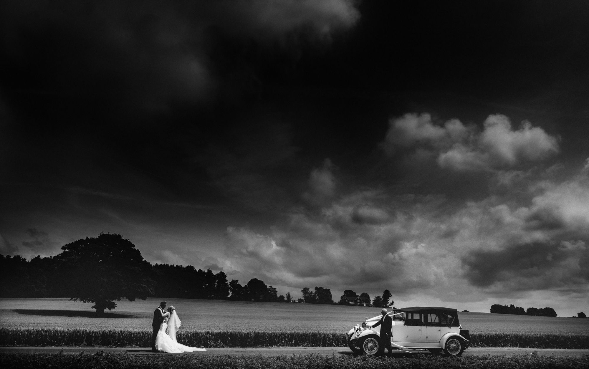 bride and groom pause for some photos by some wheat fields on their way to their wedding reception in shropshire
