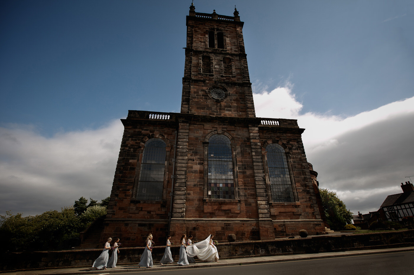 bridal party walking towards st alkmunds church in shropshire