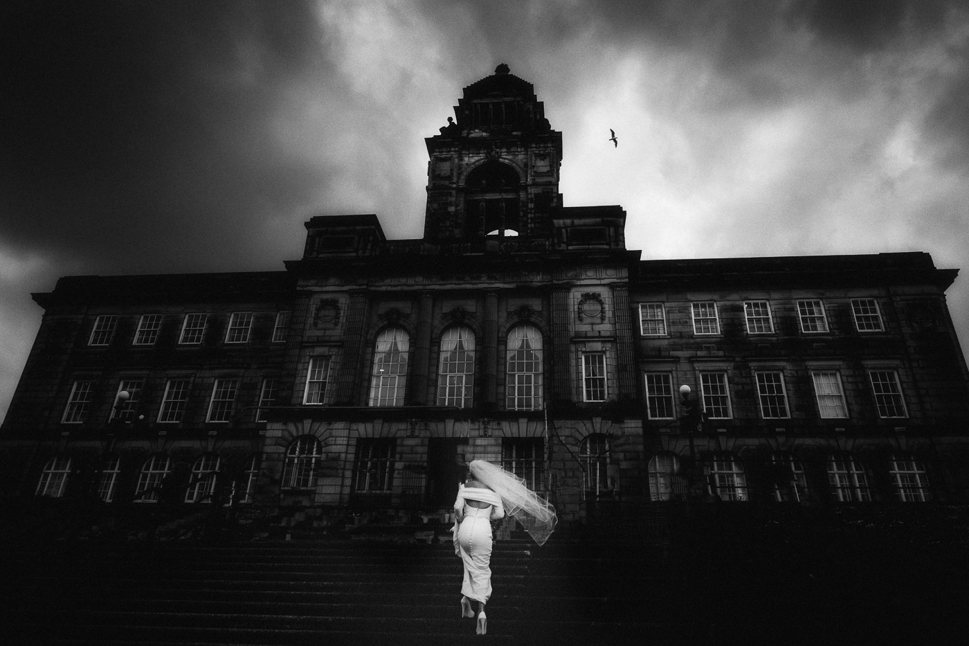 bride climbs the steps of Wallasey Town Hall in Liverpool