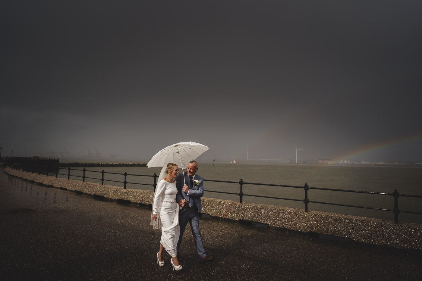 bride and groom take a walk alongside the river mersey in Liverpool
