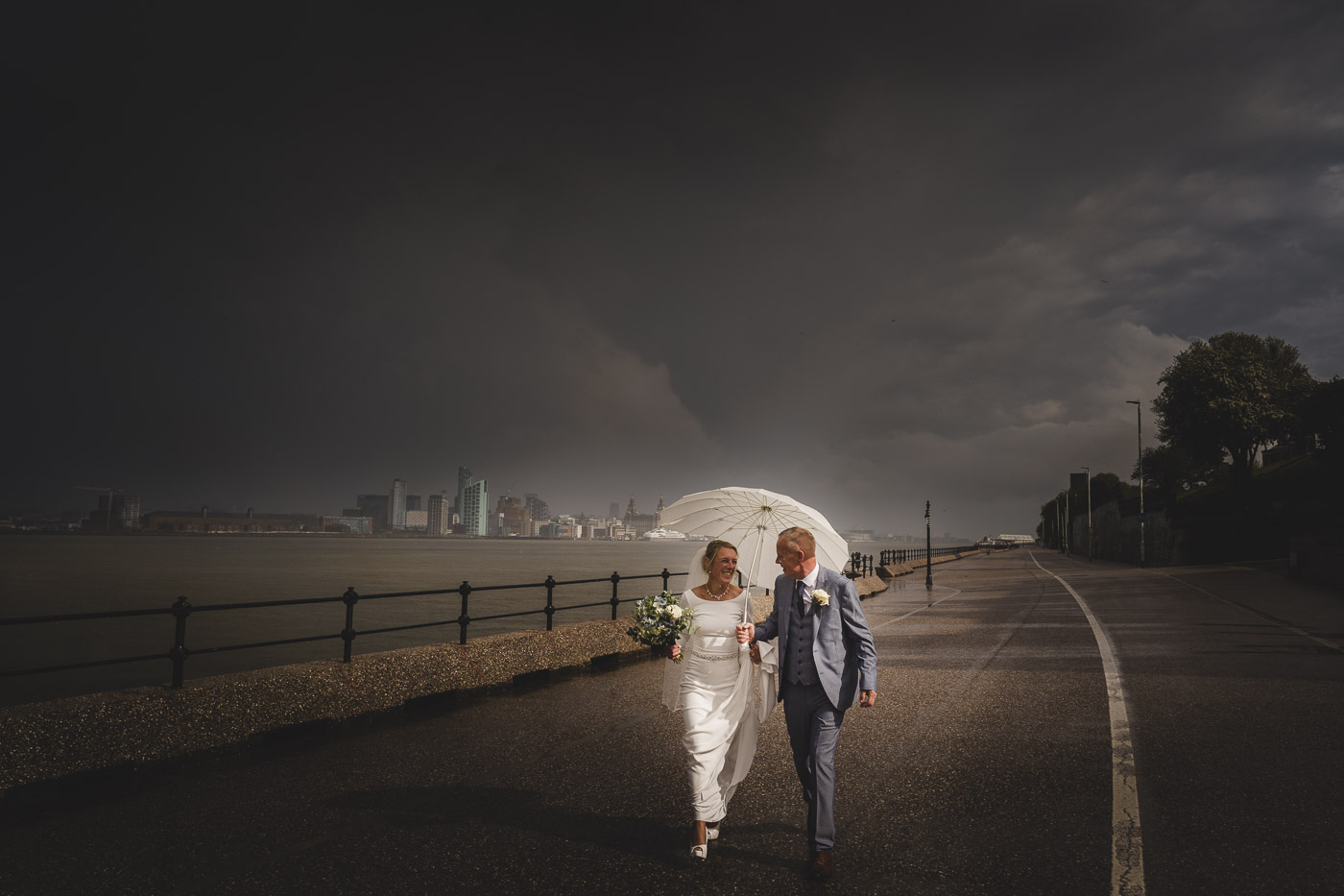 Bride and groom take a stroll alongside the River Mersey in Liverpool