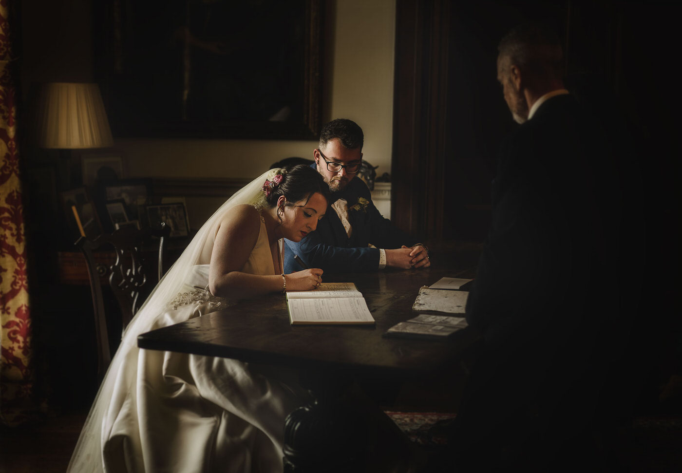 the bride and groom signing the register at a beautiful Walcot Hall Wedding