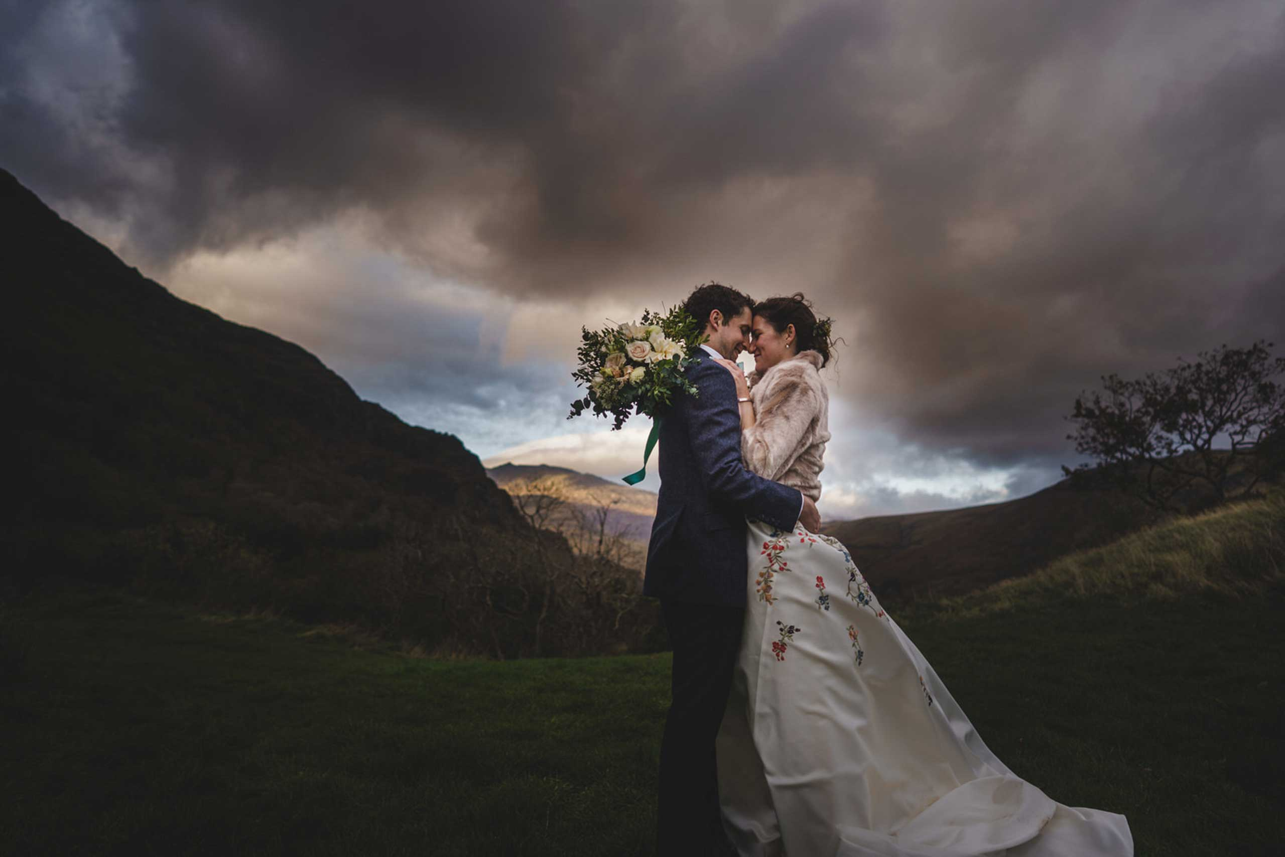 bride and groom amongst the hills with a stormy sky above at Llyn Gwynant