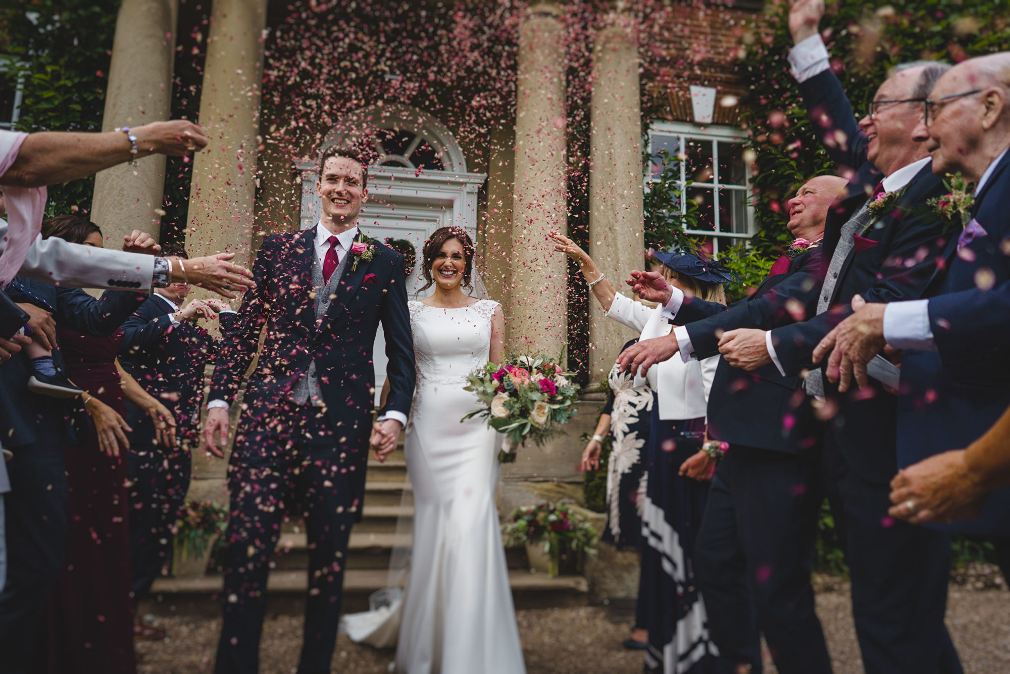 bride and groom walking through confetti at Iscoyd Park
