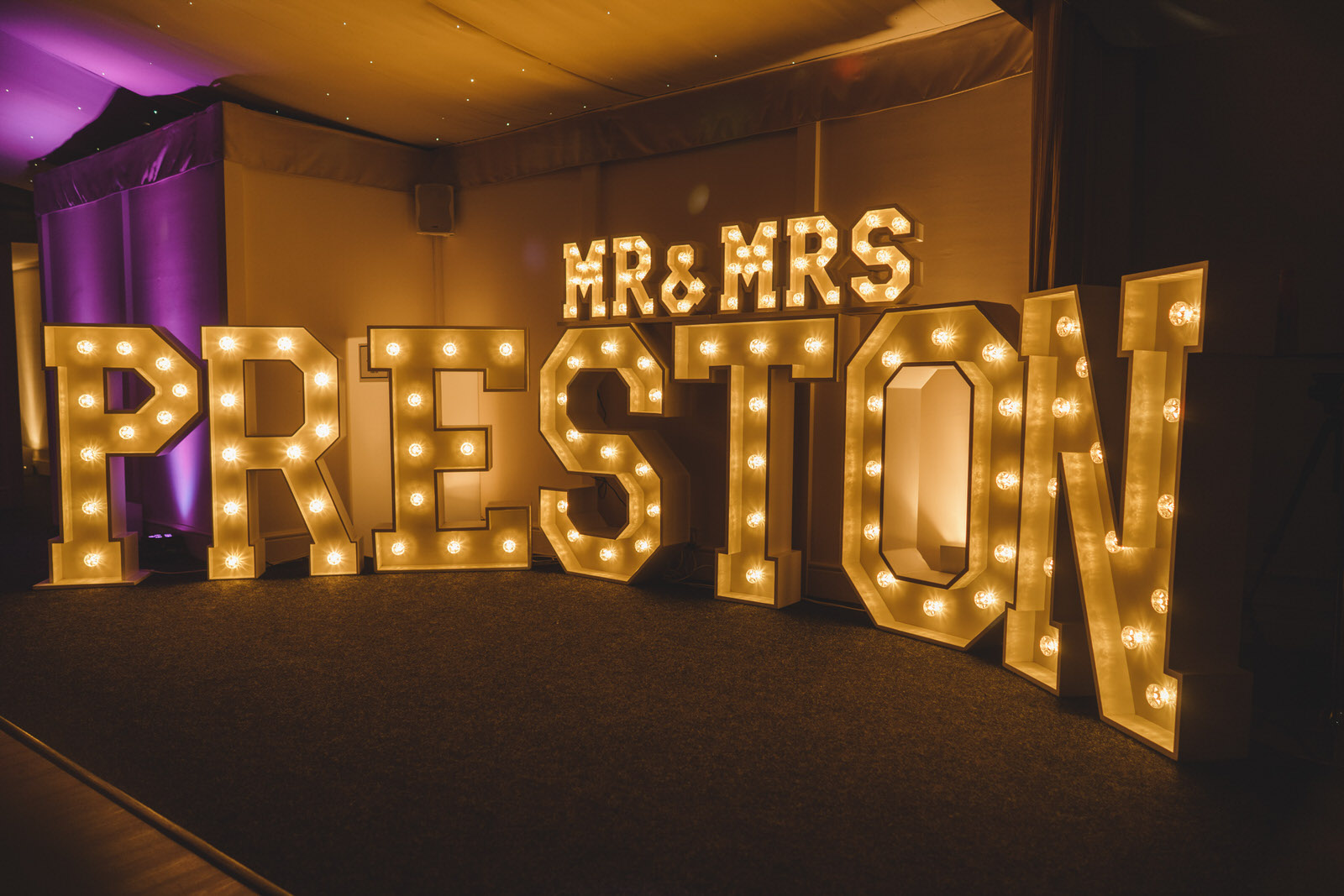 the bride and grooms names lit up in lights at their evening reception