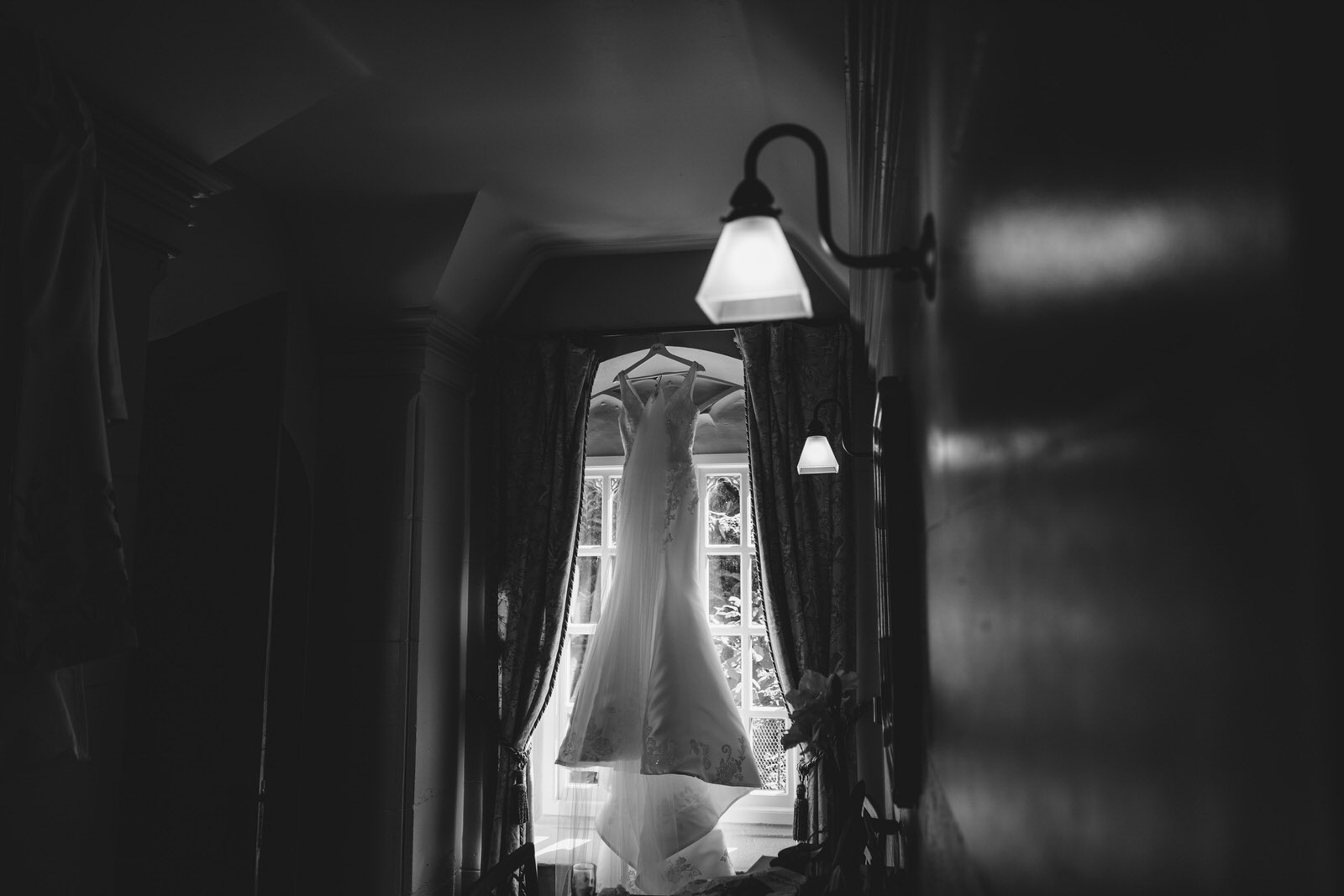 the stunning wedding dress hangs in a window at combermere abbey