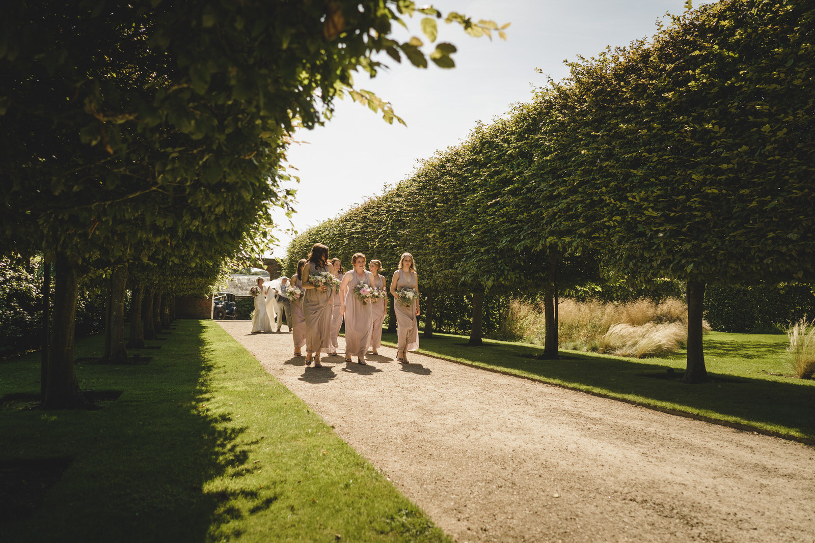 the bridal party make their way to the glasshouse at combermere abbey