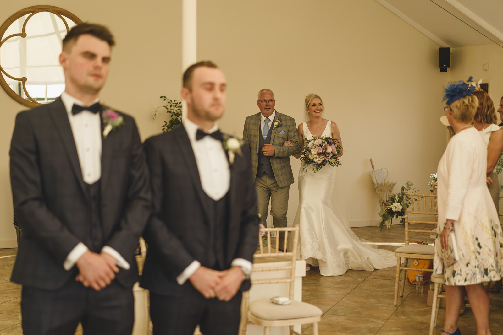 the beautiful bride makes her entrance with her father as the guests look on at combermere abbey