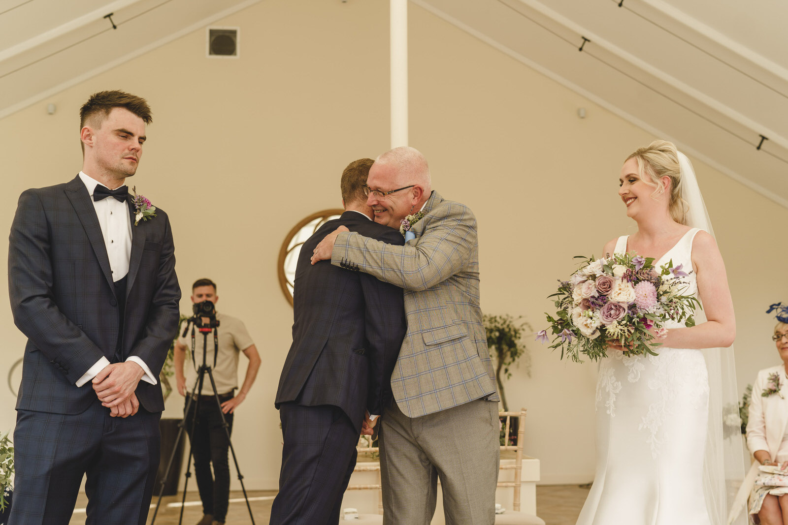 the father of the bride and the groom share a hug