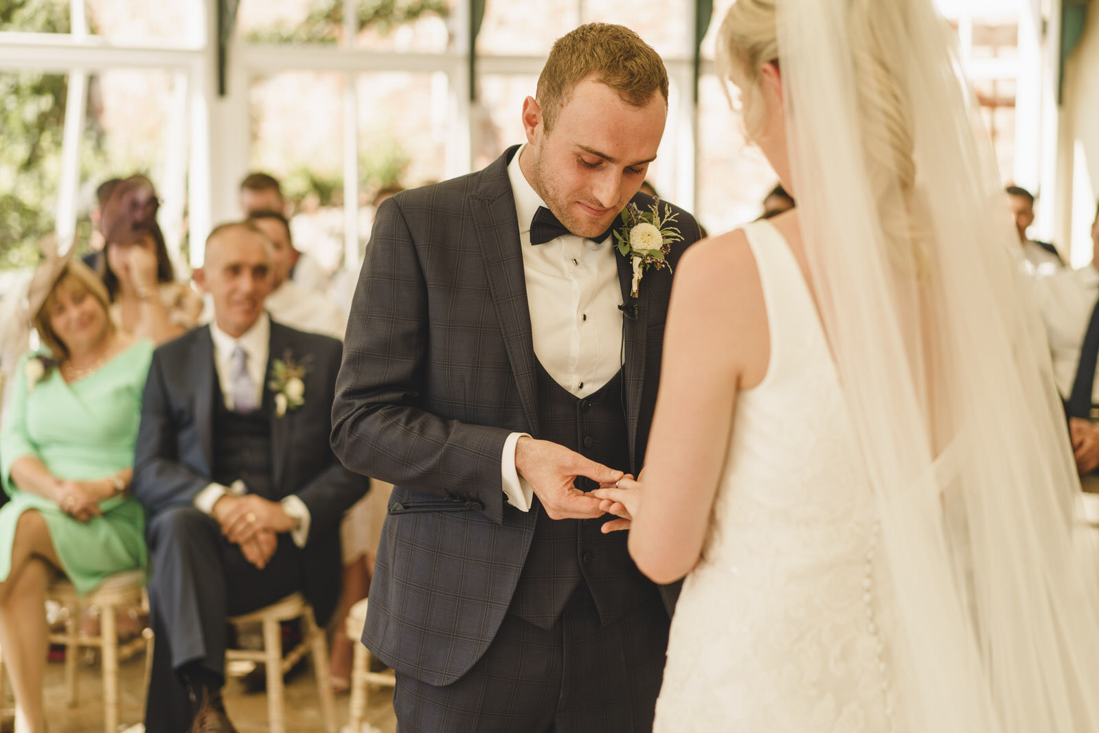 the groom carefully places the ring upon the finger of his bride
