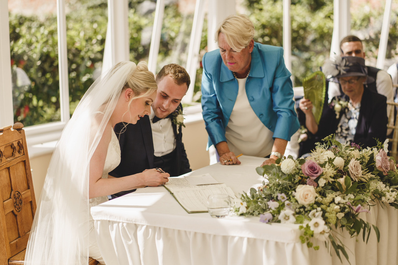 the bride signs the marriage register as the registrar and groom look on