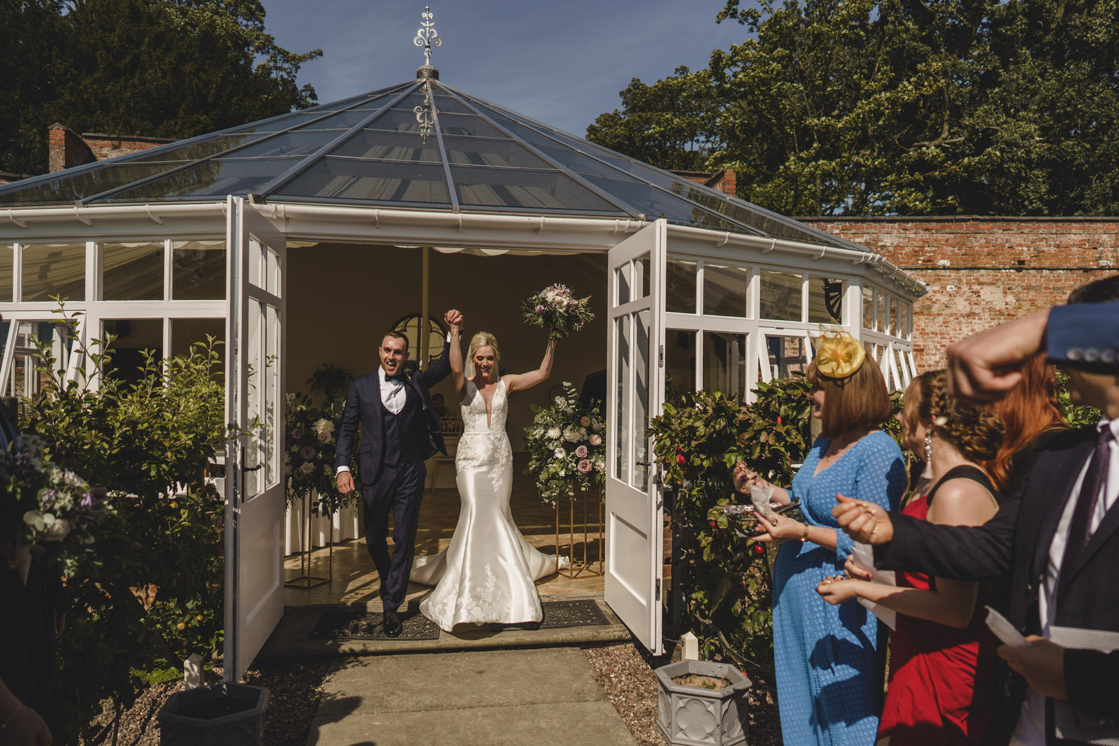 the bride and groom leave the glass house to join their waiting guests and confetti