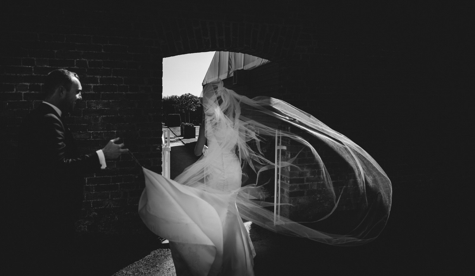 the wind catches the brides veil and creates a beautiful abstract image as the groom holds on tight to the dress