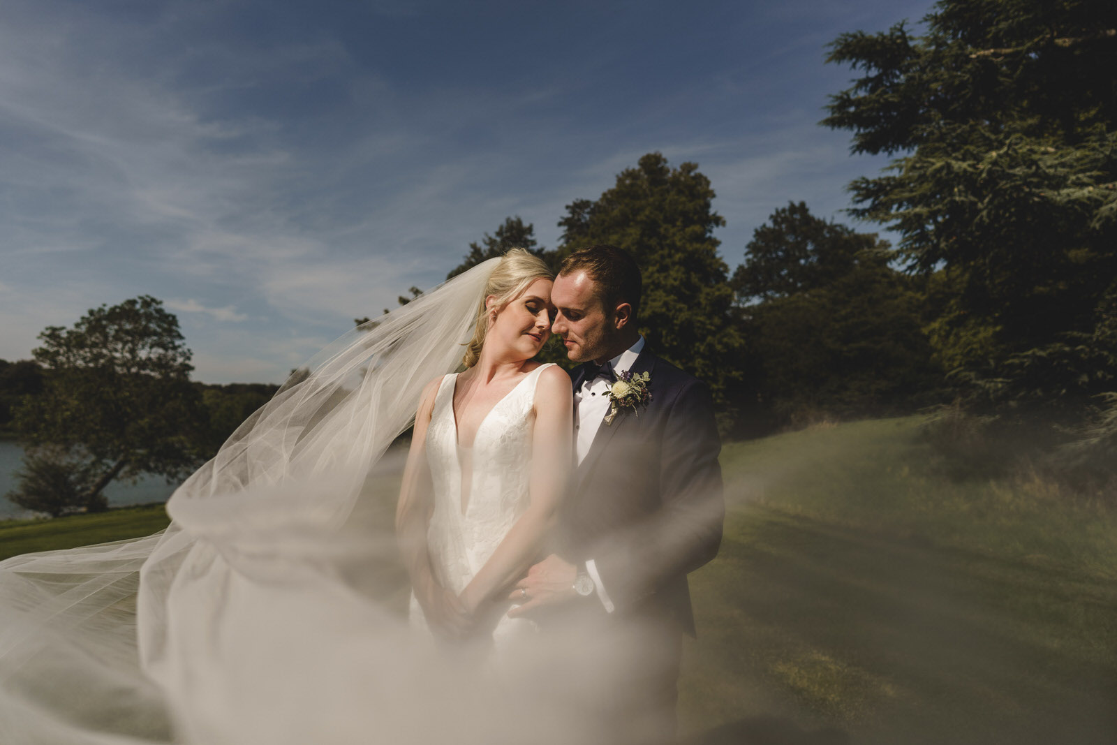 the bride and groom sharing an embrace as the brides veil is caught in the wind