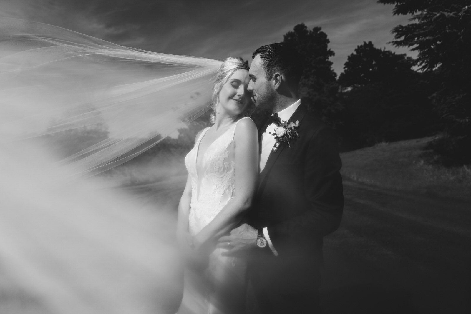 a black and white image of the bride and groom sharing an intimate moment