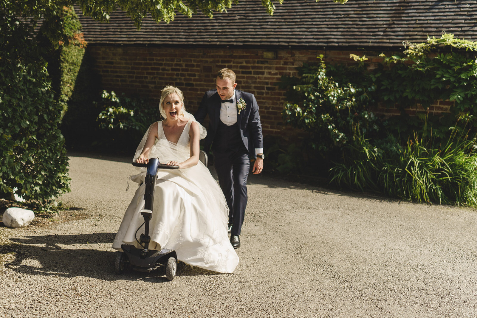 a mobility scooter makes for an interesting mode of transport for the bride as the groom looks on