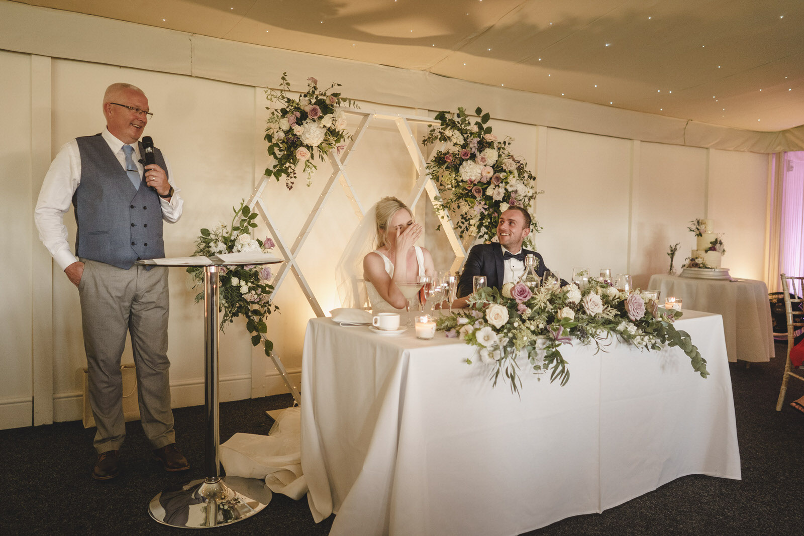 the bride's father makes her laugh at the wedding breakfast speeches