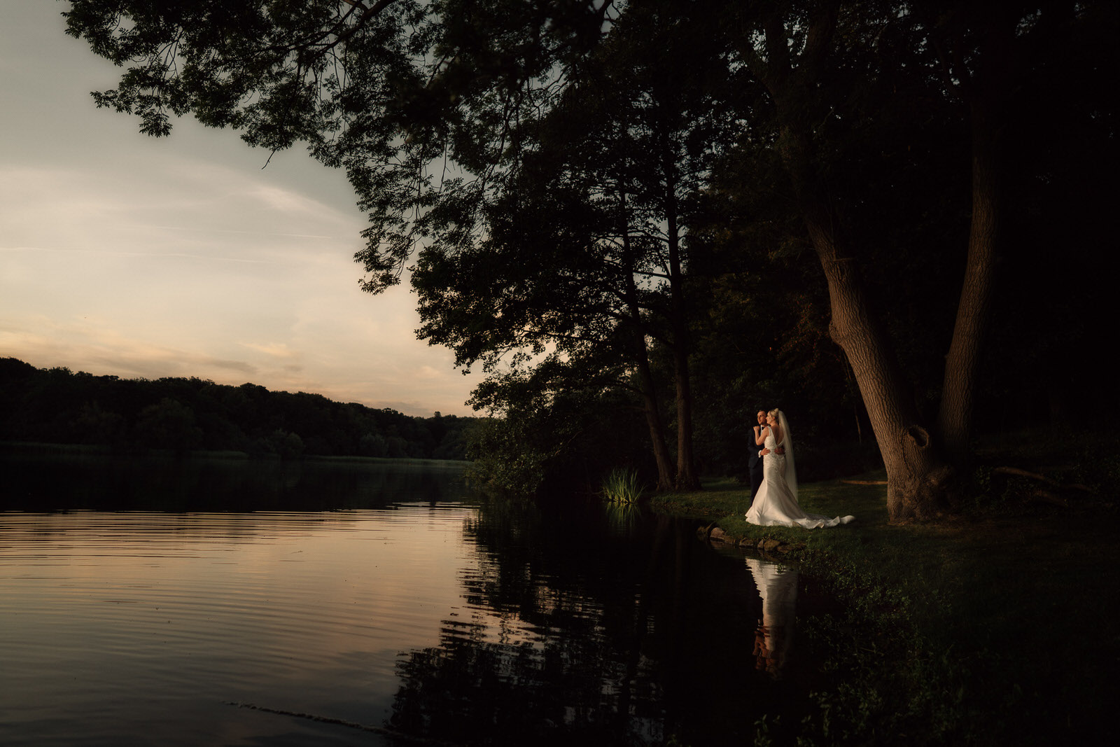 the edge of the beautiful lake is where the bride and groom stop for a few moments
