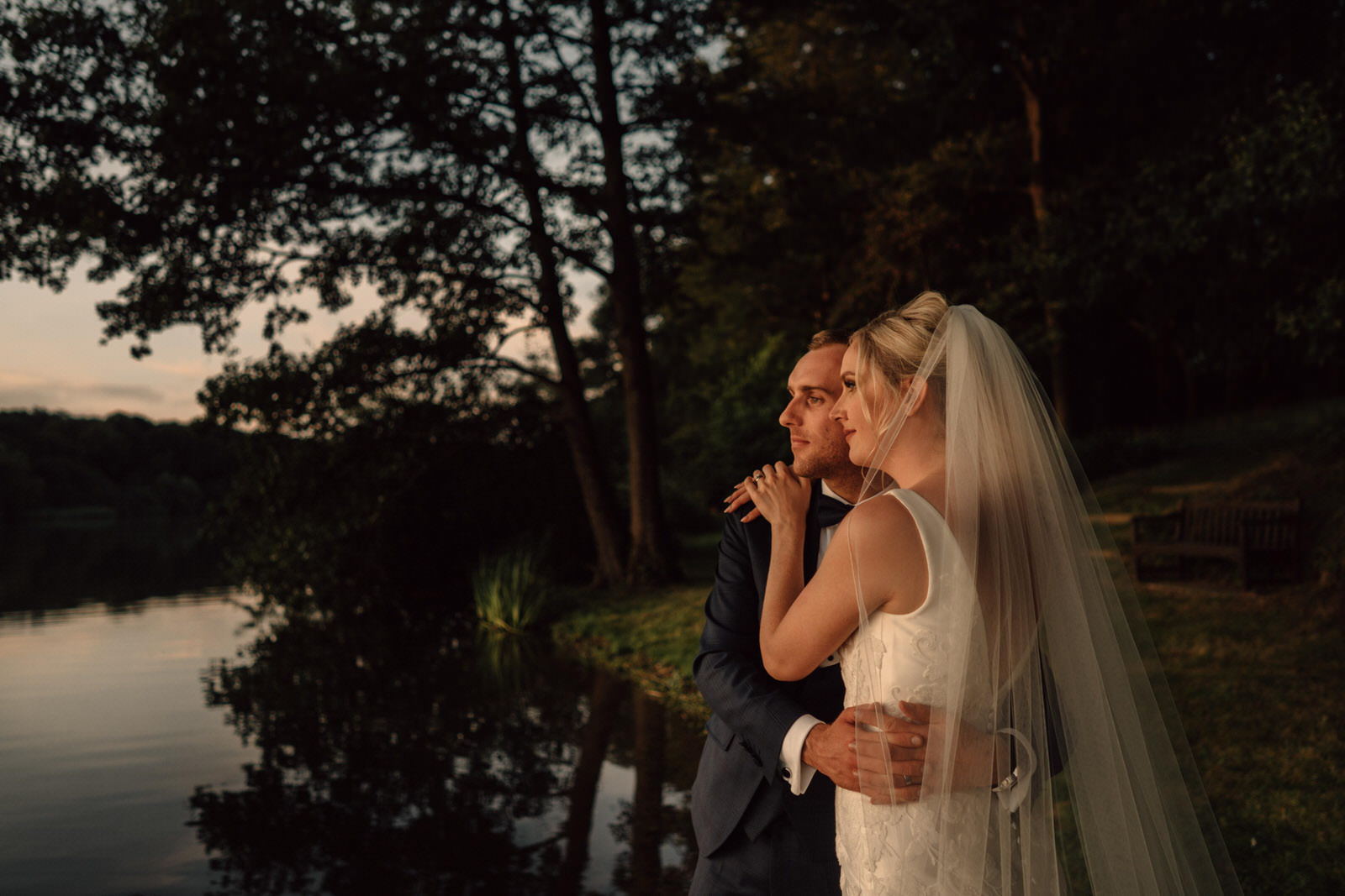 the bride and groom are bathed by sunlight by the side of the mere