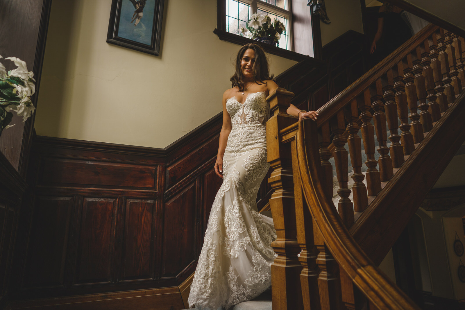 the bride makes her way down the stairs at her parental home