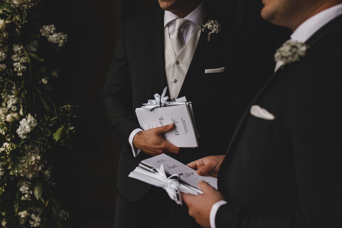 two groomsmen holding order of services await the arrival of guests
