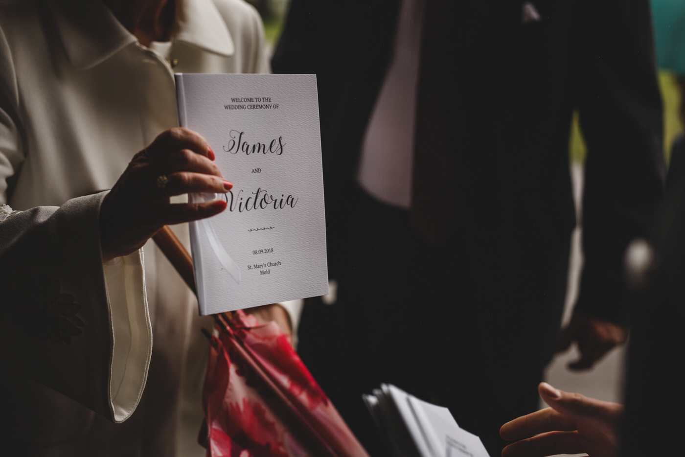 a guest holds out a copy of the wedding ceremony order of service
