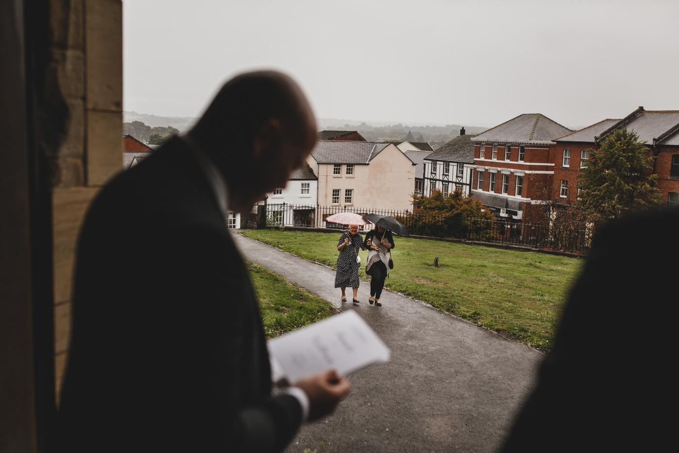 two guests walking towards the church ready for the start of the wedding