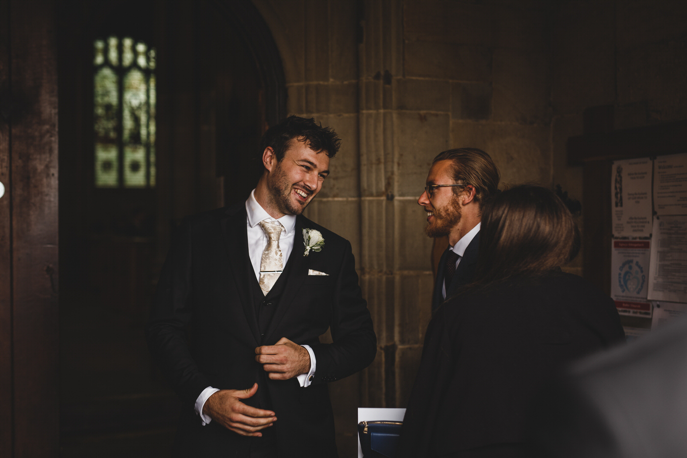 the groom welcomes guests at St Mary's church in mold