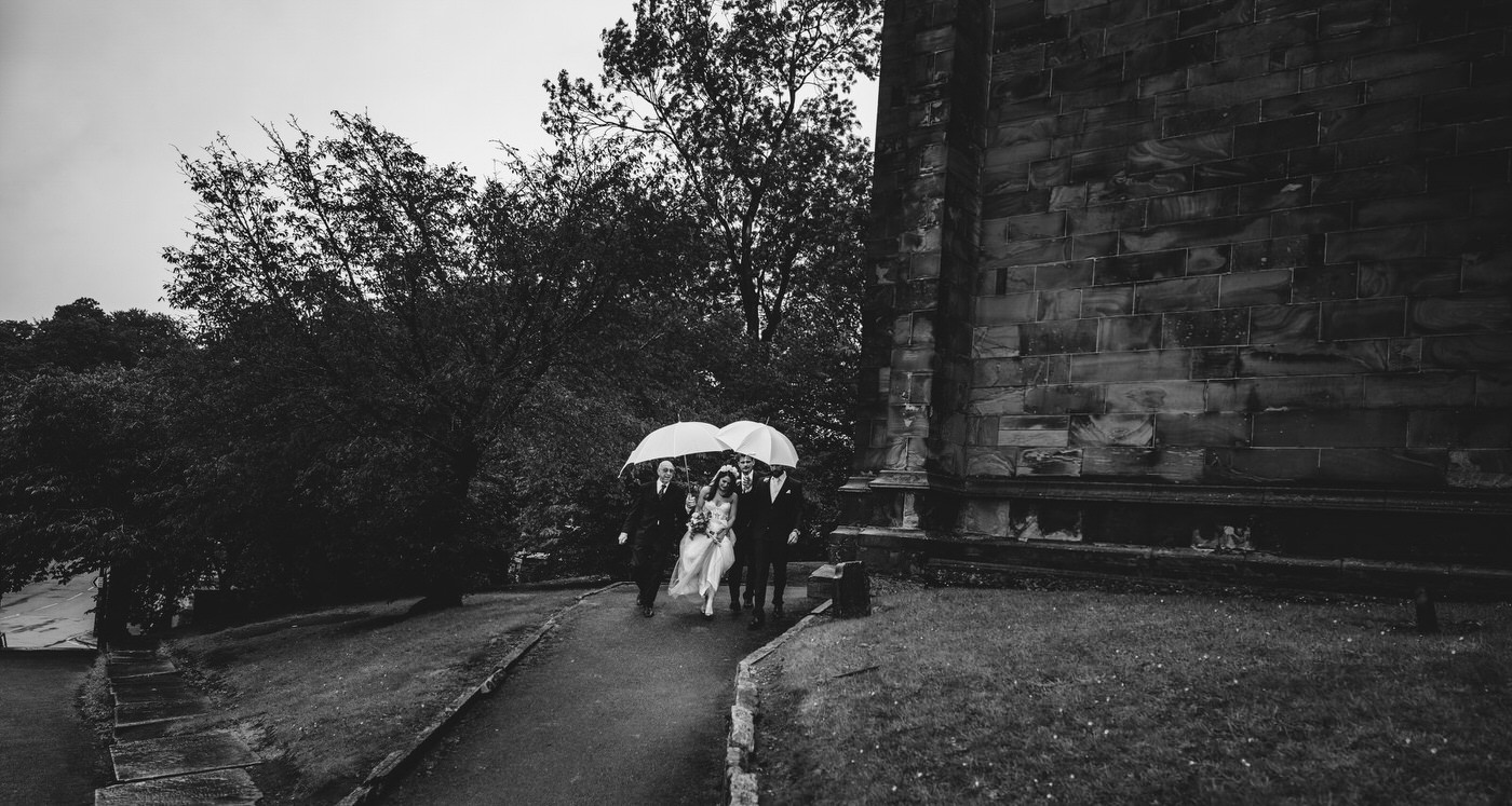 the bride is escorted to the church whilst being shielded from the rain by umbrellas