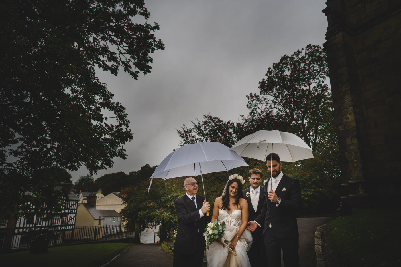 The bride makes her way to the Church while being protected from the rain with umbrellas