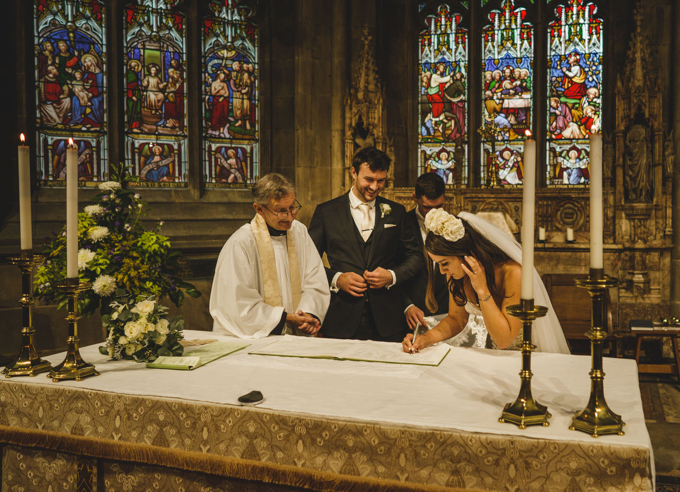 the bride signs the register as the groom and priest look on