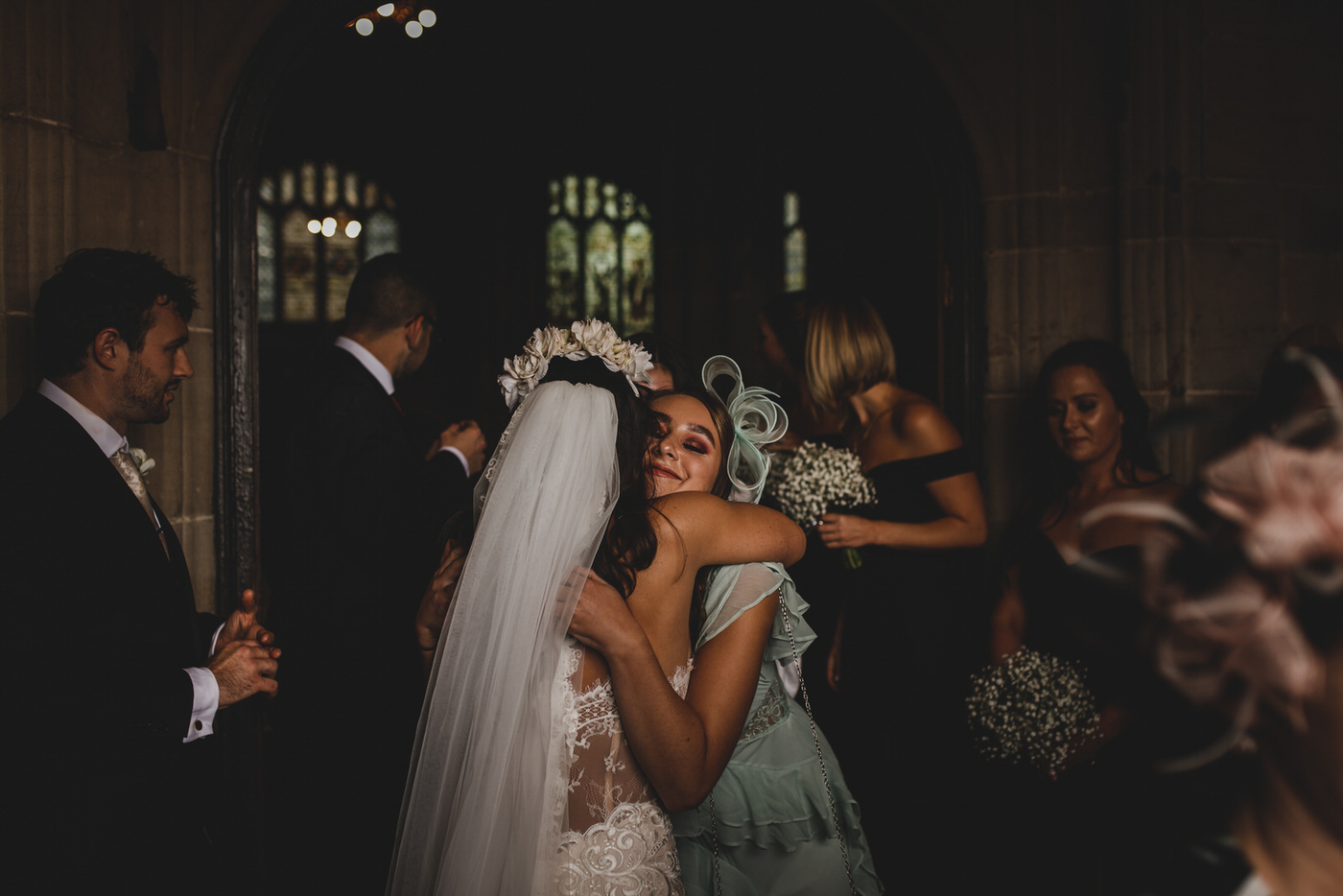a guest gives the bride a hug as they stand in the church entrance sheltering from the rain
