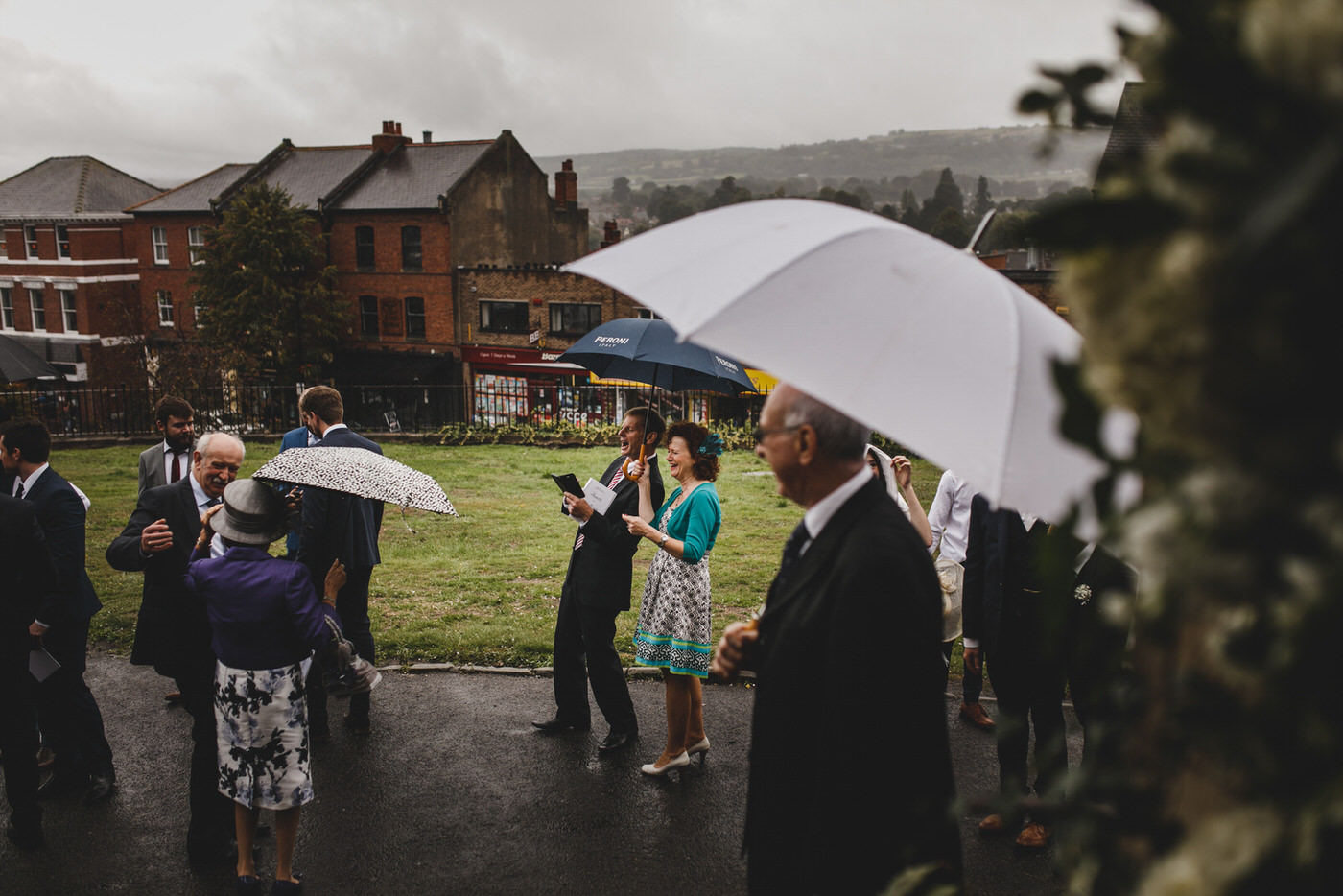 Wedding guests sheltering from the rain with brollies