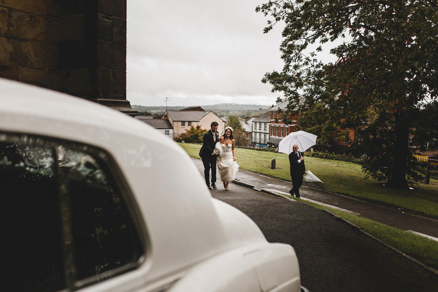 the happy couple take a short walk to the waiting wedding car