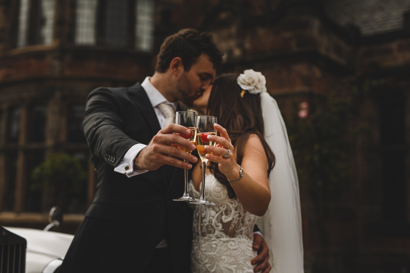 the bride and groom enjoy a kiss and a glass of champagne at Thornton Manor