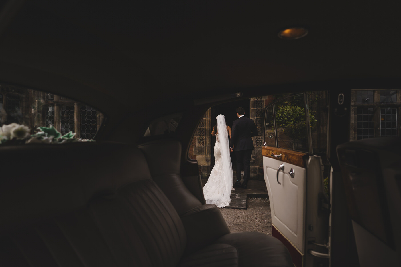 the wedding car creates a frame for the bride and groom as they enter Thornton Manor