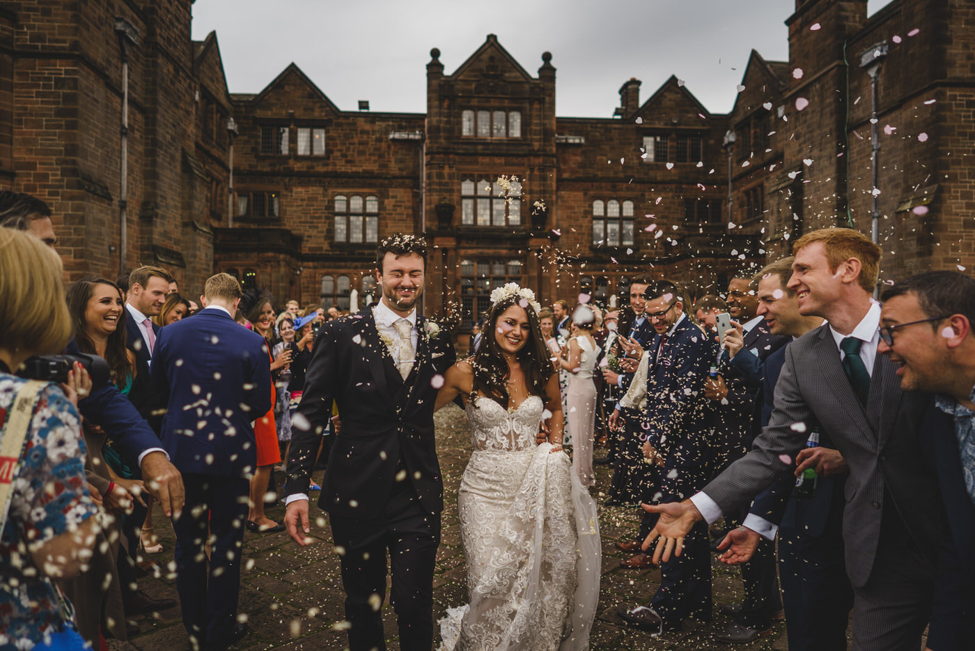 the happy couple are showered with confetti by their wedding guests