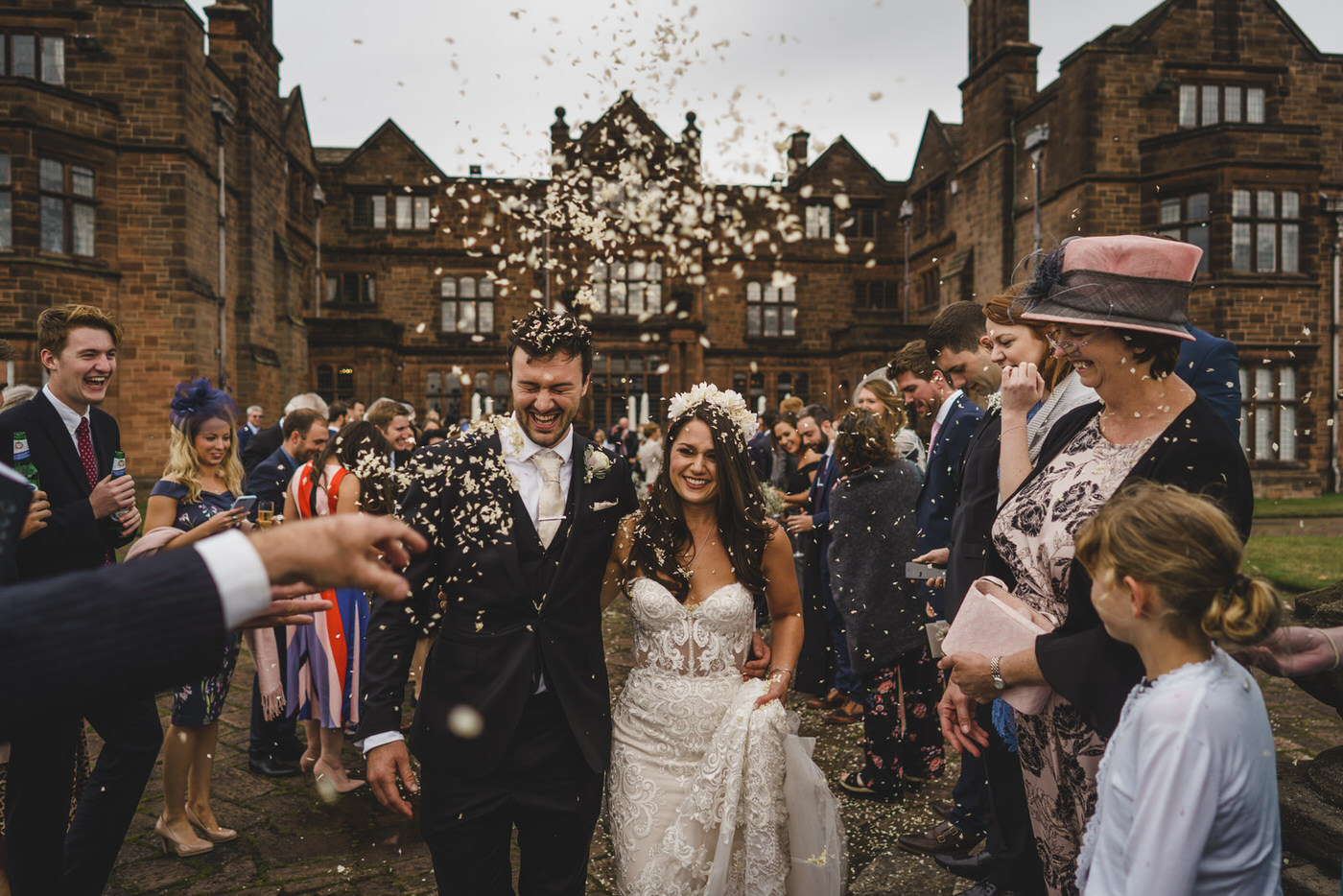 the happy couple are covered in confetti by their guests at Thornton Manor